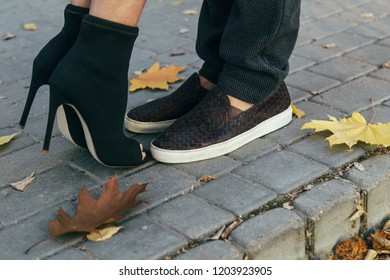 Closeup photo of male and female legs during a date in autumn park