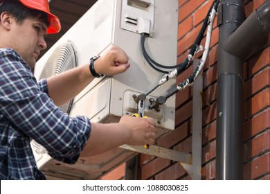 Closeup photo of male repairman connecting air conditioner pipes and tubes