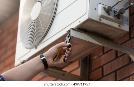 Closeup photo of male technician installing outdoor air conditioning unit
