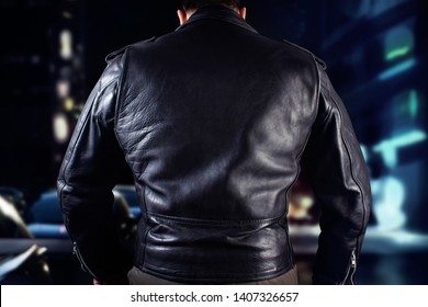Closeup photo of a man in black leather biker jacket standing on black background.