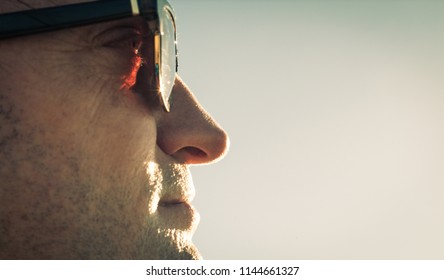 closeup photo of a man facing the sun in sunglasses