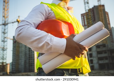 Closeup photo of man in shirt and jacket holding hardhat and blueprints on building site