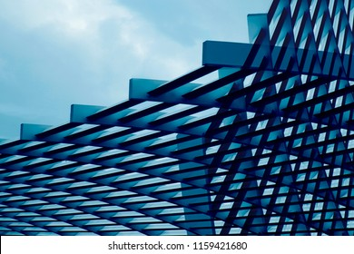 Close-up photo of metal grid structure. Abstract metallic framework background on the subject of modern architecture, building exterior, construction industry or technology.