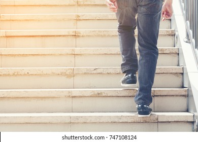 Closeup photo of modern business man walking up the stairs in rush hour to work in a hurry. During the first morning of work.