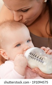 Closeup photo of mother feeding baby girl from nursing bottle, kissing head.