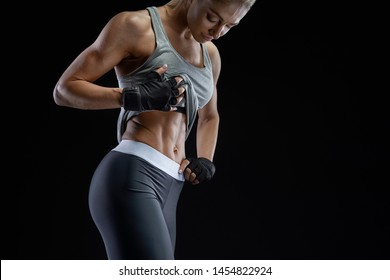 Close-up photo of muscular woman with gloved hands on hips showing off her strong abs over black background. Active lifestyle concept. Fit body workout abs training. Girl sport weight loss success