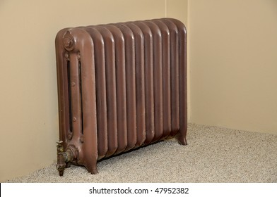 Closeup photo of an old brown room radiator.  The radiator is made of iron and is by a carpeted floor.