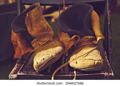 Closeup photo of old, leather shoes on a chair.