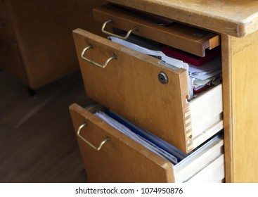 Closeup photo of old wooden desk with half-open drawers filled with papers.