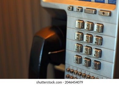 A close-up photo of pay phone in a phone booth.
