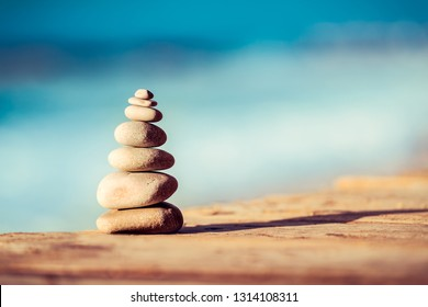 Closeup photo of a pebbles stack on the bridge over sea, spa stones, inner peace and life in balance concept