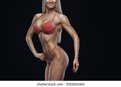 Close-up photo perfect female bikini model posing on black background Attractive female athlete bodybuilder posing demonstrate her well trained body shape arms chest booty Copy space Red swimsuit