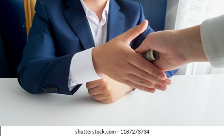 Closeup photo of person shaking hands with politician and giving him bribe