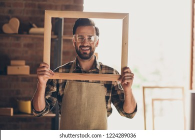 Closeup photo picture portrait of funky positive cheerful satisfied with toothy smile glad optimistic constructor foreman guy engineer holding large big frame in hands looking at camera