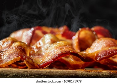 Closeup photo of a pile of freshly cooked hot crispy bacon resting on a wood cutting board
