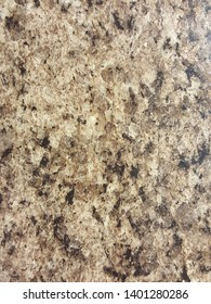 Closeup photo of polished granite texture with beige, brown, and black hues.Background image for posters, flyers, and brochures