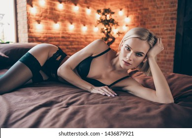 Closeup photo portrait of graceful charming gorgeous stunning attractive lady mistress stripper prostitute lying down on soft linen in loft room indoors hotel waiting for partner to have intercourse