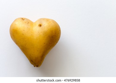 Close-up photo of potato in a shape of heart on white background