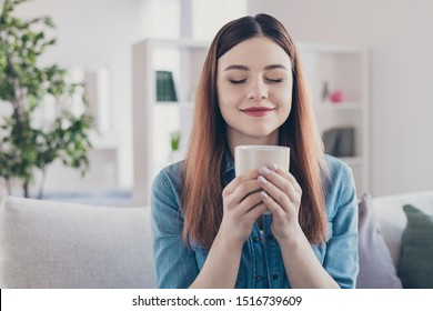 Closeup photo of pretty dreamer lady holding hot beverage in hands enjoy amazing drink smell sitting on sofa wearing jeans clothes homey apartment indoors