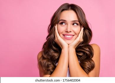 ほおの上のとてもうれしそうな表情の腕が空っぽに見える、かなりおかしな波状の女性の接写写真で、白い一重項明るいピンクの色の背景を身に着けている。