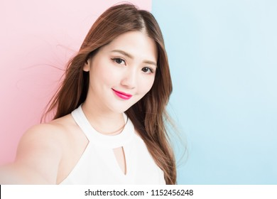 Close-up photo of pretty girl making selfie photo on smart phone isolated on a pink and blue background.