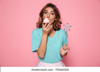 0b982a04efc Close-up photo of pretty young girl with magic wand eating delicious  cupcake
