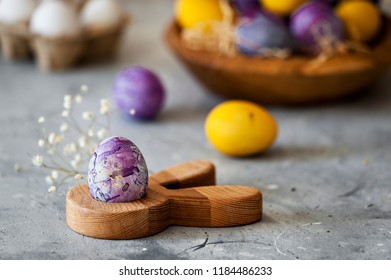 Close-up photo of purple and yellow Easter eggs on concreted table with blurred background