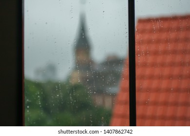 The closeup photo of the raindrops on the blurred Kaliningrad cathedral behind the roof background. Natural weather and Kaliningrad architecture background