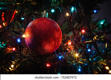 Closeup photo of red Christmas ball and garland on fir tree. Christmas night. Dackground with copy space.