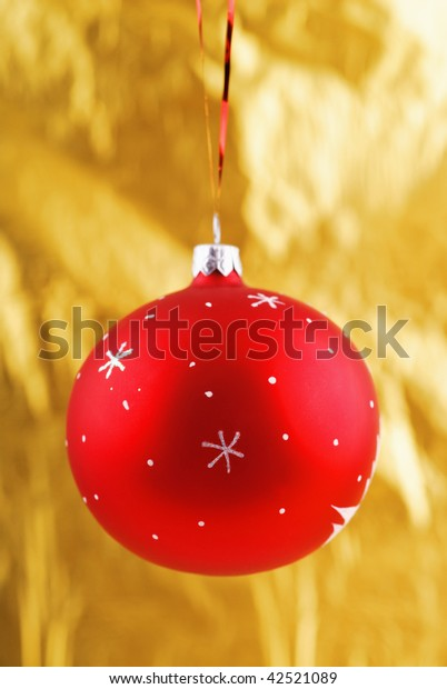 Close-up photo of red  christmas ball over yellow background