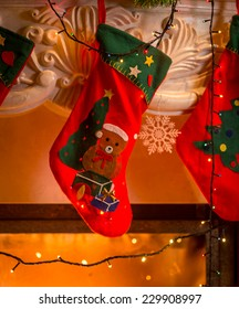 Closeup photo of red christmas stockings hanging on fireplace
