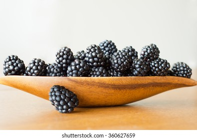 A closeup photo of ripe blackberries on wooden plate.