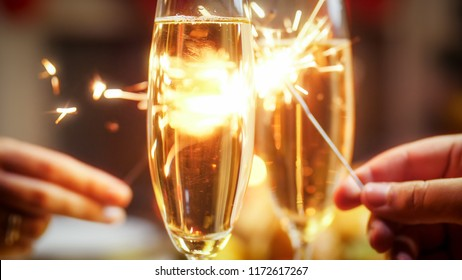 Closeup photo of romantic couple burning sparklers and drinking champagne on festive dinner
