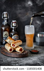 Close-up photo of salty appetizing snack with meat on wooden board with bottles and blurred beer in glass on concreted table background