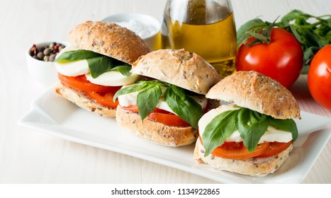 Close-up photo of sandwich, burger with caprese salad with ripe tomatoes, basil, buffalo mozzarella cheese. Italian and Mediterranean food concept. Fresh and healthy organic meal. Starter and antipast