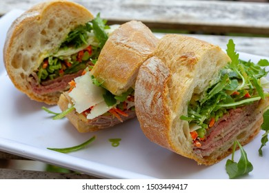 Closeup photo of a sandwich cut into three pieces on a white plate. Ingredients are slices of meat, arugula, sliced carrots and Swiss cheese.
