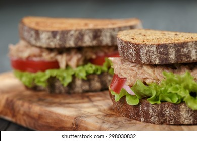 closeup photo of sandwich with tuna and vegetables on rye bread on wood background