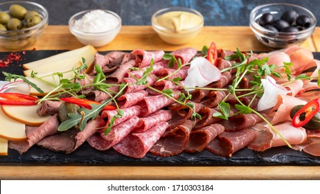 Closeup photo of sausages and smoked meats on wooden board.