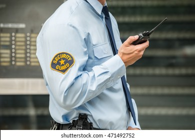 Close-up Photo Of Security Guard Using Walkie-talkie