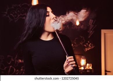 Close-up photo of a seductive brunette girl in black top smokes a hookah in nightclub or hookah bar.
