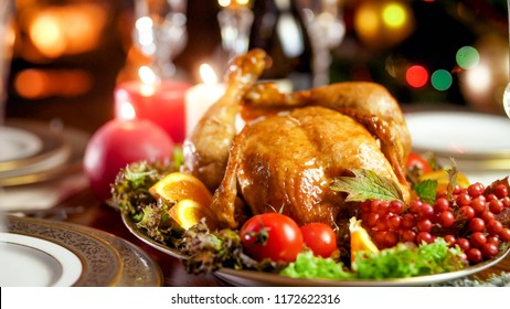 Closeup photo of served Christmas dining table against burning fireplace and glowing colorful lights