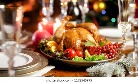Closeup photo of served family festive table against glowing Christmas tree and burning fireplace