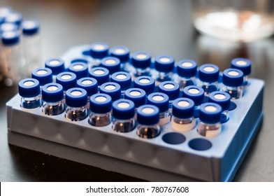 A close-up photo of a set of blue high pressure liquid chromatography (HPLC) vials on a rack for chemical analysis in a medical/pharmaceutical laboratory.