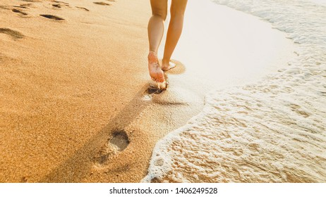 Closeup photo of sexy barefoot female feet walking on the wet sand and calm warm waves at sea beach