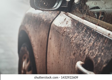 Closeup photo shoot of dirty car's mirror, door and window, splash and texture of mud on silver car.