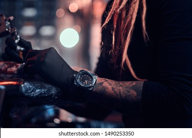 Closeup photo shoot of tattoo making, artist is working with tattoo machine on customer's hand.