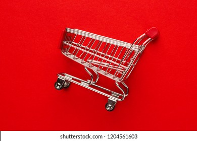close-up photo of shopping trolley on red background. minimalistic photo of pushcart