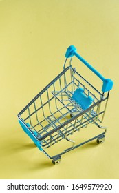 close-up photo of shopping trolley on yellow background.Top view of minimalistic photo of pushcart