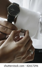 a close-up photo shot when the bride is preparing the groom, putting on cuff links.