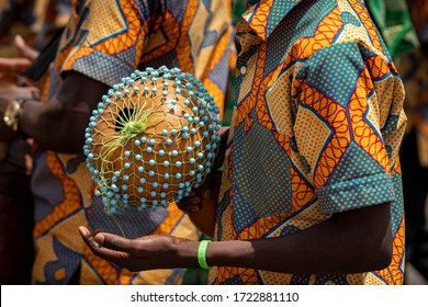 A closeup photo shows a drummer playing an African Shekere gourd percussion instrument while marching in a procession during a kente yam festival in Ghana, West African